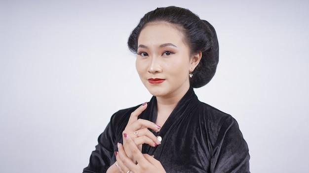Aziatische vrouw in zwarte kebaya ziet er vrouwelijk uit geïsoleerd op een witte achtergrond