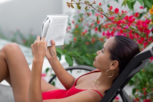 Aziatische vrouw in zwembroek ontspannen bij zwembad op zonnebank gelezen boek bij villa door kleurrijke bloemboom