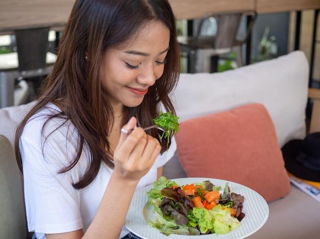 Aziatische vrouw is blij om zalmsalade te eten
