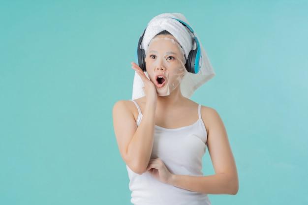 Aziatische vrouw is gezichtsmasker. ze luistert naar vrolijke muziek en verrassing.