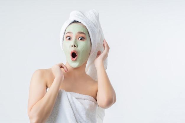 Aziatische vrouw is gezichtsmaskers. ze is blij en verrast.