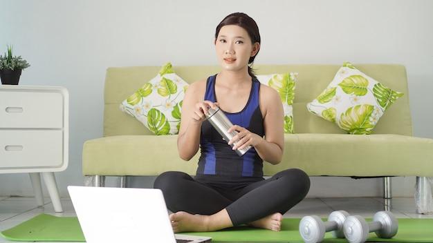Aziatische vrouw is klaar met yoga terwijl ze thuis naar haar laptopscherm kijkt