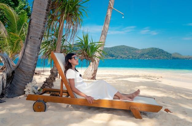 Aziatische vrouw is witte jurk en zonnebril zit op de strandstoel en ontspant op het strand van de blauwe zee-eilanden, toeristisch meisje ontspant op vakantie onder kokospalmen, rayang-eiland, rayong, thailand