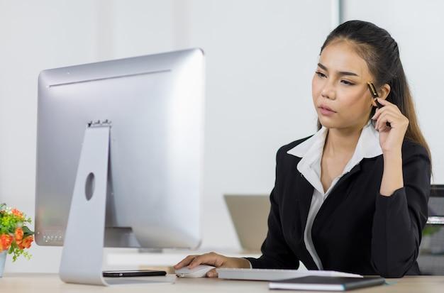 Aziatische vrouw kantoormensen zitten aan een bureau en gebruiken de computer terwijl ze serieus denken zoals bedoeld op kantoor.