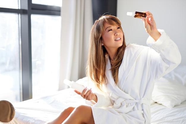 Aziatische vrouw kijkt naar de rest van het serum in de flacon zittend op bed, ze gaat cosmetica gebruiken, aanbrengen op de huid, schoonheidsprocedure thuis