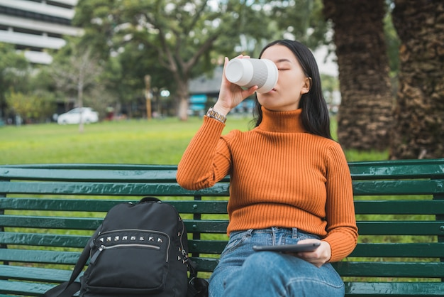 Aziatische vrouw koffie drinken en het gebruik van een tablet.