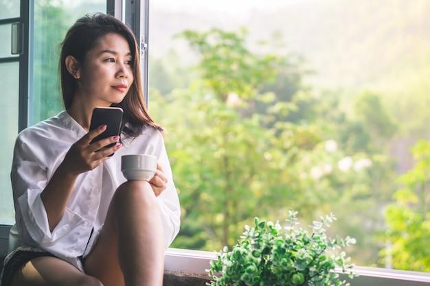 Aziatische vrouw koffie drinken en slimme telefoon gebruiken