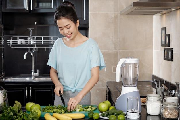 Aziatische vrouw kookt salade in de keuken