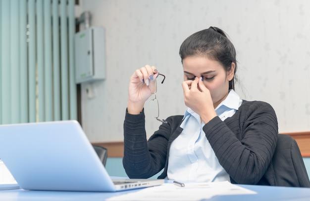 Aziatische vrouw kreeg de hele dag hoofdpijn van het werken aan een notebook, computer vision syndrome