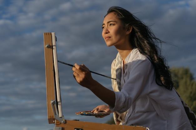 Aziatische vrouw kunstenaar schilderij foto op canvas, met penseel en palet
