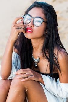 Aziatische vrouw l poseren op tropisch strand in de avond. perfect gebruind lichaam. sieraden, armband en ketting.