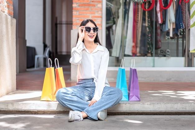 Aziatische vrouw lachend met boodschappentassen te houden