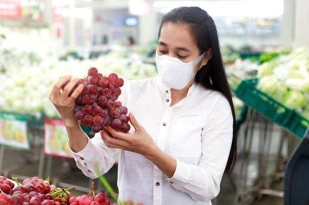 Aziatische vrouw lang haar dragen van beschermend gezichtsmasker in supermarkt warenhuis.