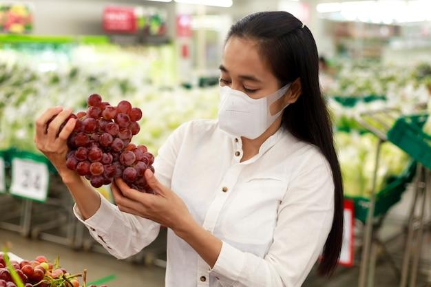 Aziatische vrouw lang haar dragen van beschermend gezichtsmasker in supermarkt warenhuis