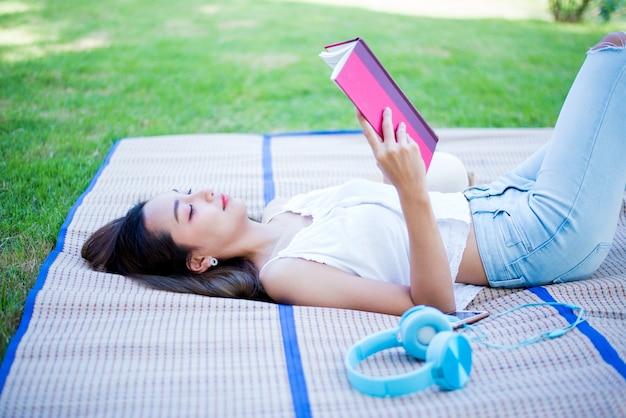 Aziatische vrouw leesboek alleen in het park op lentedag. ontspan en recreatie. outdoor activiteit en levensstijl op vakantie.