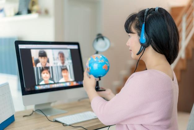Aziatische vrouw leraar aardrijkskunde lesgeven via videoconferentie e-learning