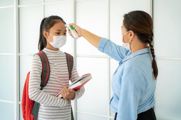 Aziatische vrouw leraar met behulp van thermometer screening student voor koorts