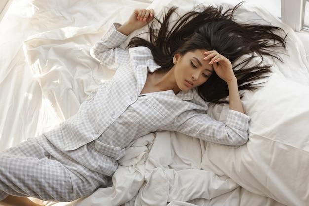 Aziatische vrouw liggend op het bed