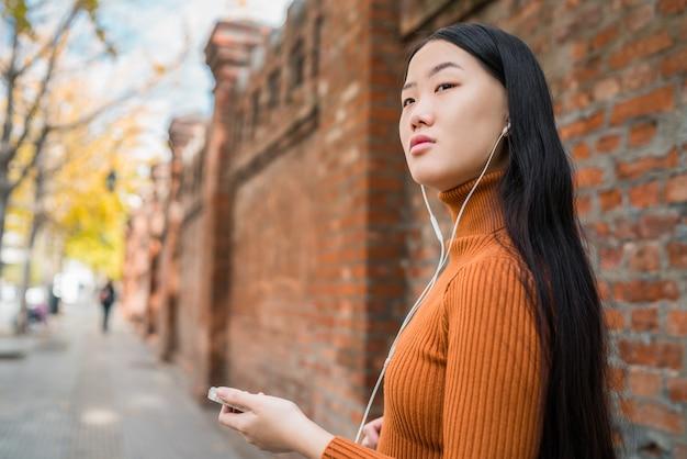 Aziatische vrouw luisteren muziek.