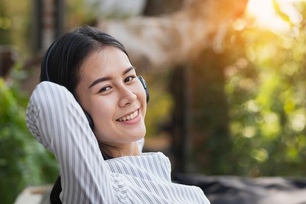 Aziatische vrouw luisteren naar muziek met ontspannen en gelukkig in vrije tijd.
