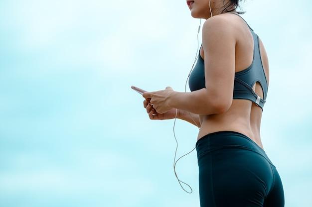 Aziatische vrouw luistert naar muziek van haar mobiele telefoon tijdens het hardlopen in de ochtendfitness