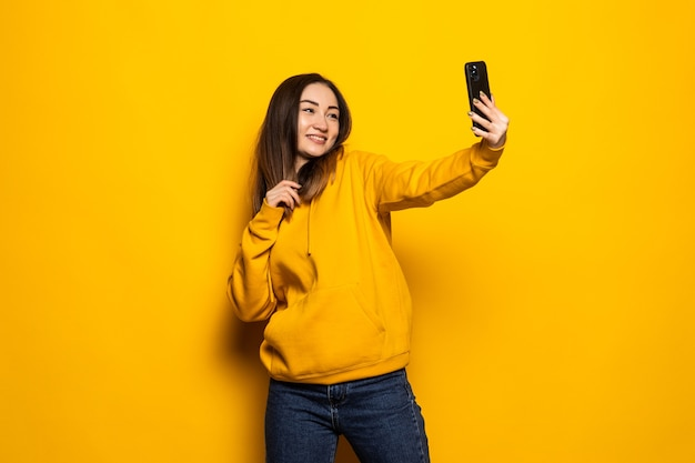 Aziatische vrouw maakt selfie foto op smartphone op gele muur