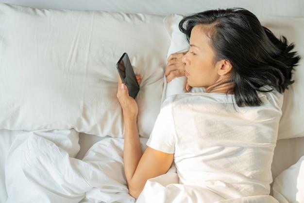 Aziatische vrouw met aantrekkelijke de tabletsmartphone van het glimlachgebruik op wit bed. bovenaanzicht