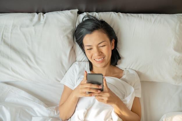 Aziatische vrouw met aantrekkelijke glimlachgebruiksmartphone op wit bed.