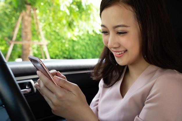 Aziatische vrouw met behulp van de mobiele telefoon en geniet van berichten met vriendengroep na het reizen op de laatste vakantie in haar auto