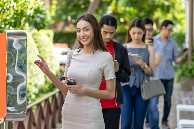 Aziatische vrouw met behulp van kiosk van voedsel bestellen met sociale afstand wachtrij in de rij voordat u in fastfoodrestaurant