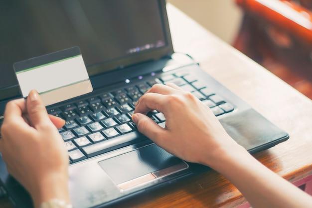 Aziatische vrouw met behulp van laptop en creditcard online winkelen, selectieve aandacht aan kant, soft focus en vi