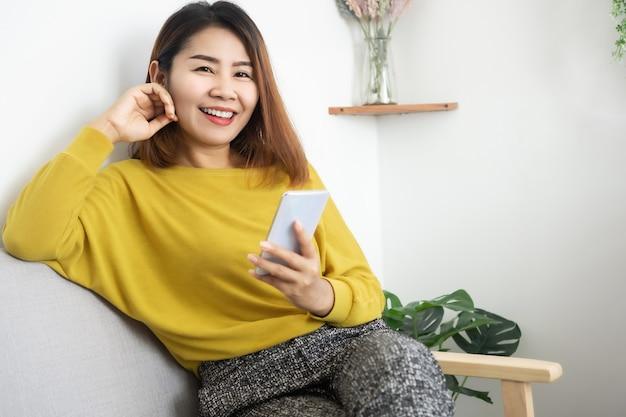 Aziatische vrouw met behulp van mobiele telefoon zittend op de bank glimlachen naar een camera