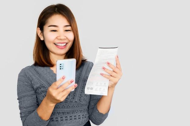Aziatische vrouw met behulp van slimme telefoon scannen qr-code bij het online betalen van factuur