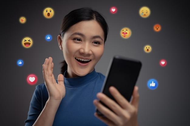 Aziatische vrouw met behulp van slimme telefoon voor sociale media met emoticon zeepbel. geïsoleerd