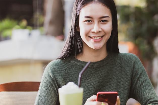 Aziatische vrouw met behulp van smartphone en het drinken van drank met ontspannen plezier en gelukkig