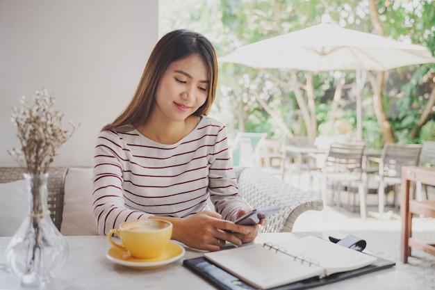 Aziatische vrouw met behulp van smartphone in koffie cafe
