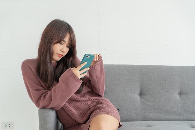 Aziatische vrouw met behulp van smartphone op grijze bank in de woonkamer