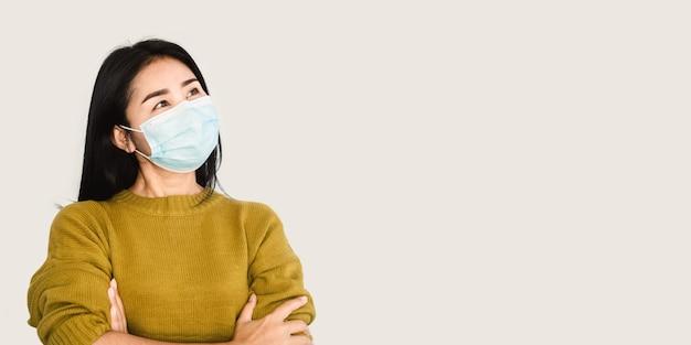 Aziatische vrouw met beschermend gezichtsmasker over grijze bannerachtergrond