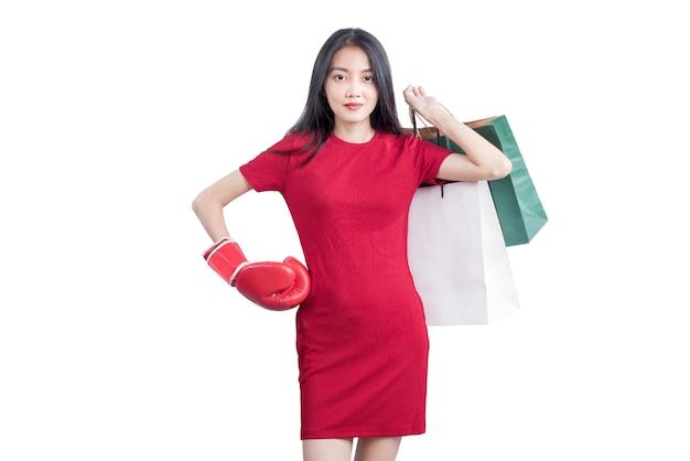 Aziatische vrouw met bokshandschoen met boodschappentassen geïsoleerd op witte achtergrond