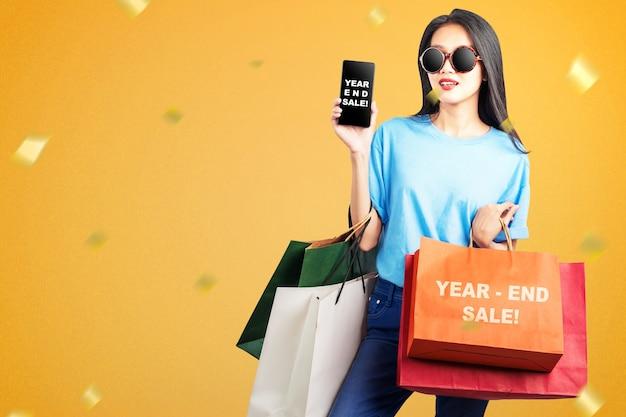 Aziatische vrouw met boodschappentassen die het scherm van de mobiele telefoon met de tekst van de eindejaarsverkoop tonen. gelukkig nieuwjaar 2021