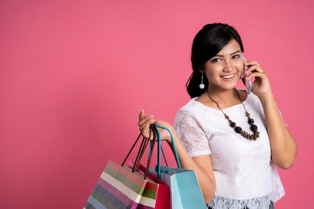 Aziatische vrouw met boodschappentassen en telefoon