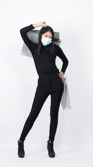 Aziatische vrouw met boodschappentassen in haar hand en medische gezichtsmasker dragen