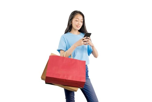 Aziatische vrouw met boodschappentassen met mobiele telefoon geïsoleerd op witte achtergrond