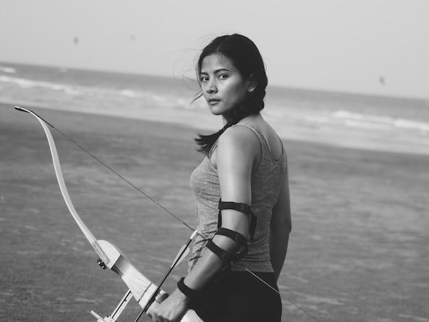 Aziatische vrouw met boog boogschieten