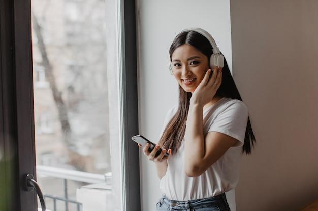 Aziatische vrouw met bruine ogen in witte top kijkt naar de voorkant met een glimlach, houdt een smartphone en zet een koptelefoon op