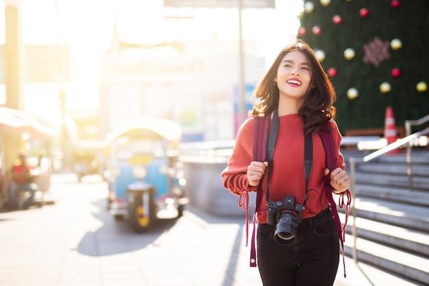 Aziatische vrouw met camera lopen op straat