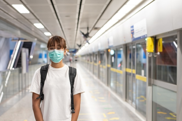 Aziatische vrouw met chirurgisch gezichtsmasker moe voelen gebruik smartphon staan wachten op metro, skytrain, rugzak dragen, reizen naar de stad, sociale afstand nemen, coronavirus, covid19