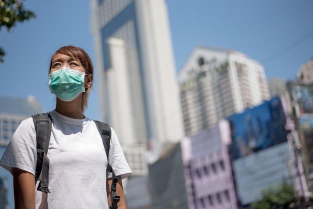 Aziatische vrouw met chirurgisch gezichtsmasker, rugzak draagt, reist naar de stad staande op viaductbrug, sociale afstand, coronavirus, covid19