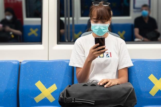 Aziatische vrouw met chirurgisch gezichtsmasker voelt moe gebruik smartphone zittend op blauwe stoel in de metro