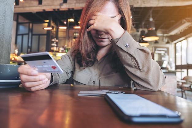 Aziatische vrouw met creditcard met gevoel gestrest en blut, mobiele telefoon op tafel
